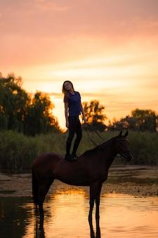 浅い湖で馬に乗る少女、