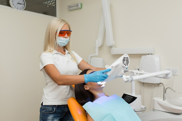 Отбеливание зубов с помощью ультрафиолетового отбеливающего устройства, ассистент стоматолога, ухаживающий за пациентом, глаза защищены очками, отбеливающая процедура с использованием света, лазера, фтора, искусственное отбеливание зубов