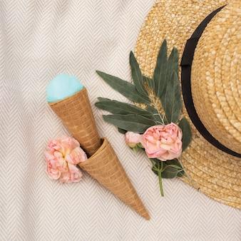 Голубое мороженое в вафельном рожке лежит возле соломенной шляпы