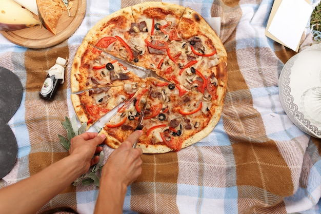 日曜日の公園でピクニックにピザをカットします。
