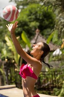 Молодая сексуальная женщина в розовом купальнике играет с мячом в тропическом муху, в красивой балийской сцене джунглей,
