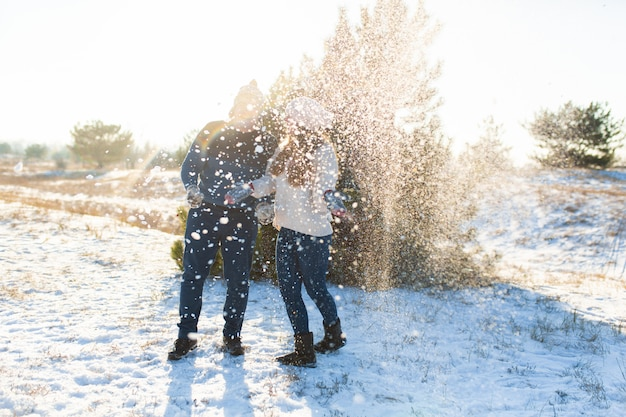 愛するカップルが森で冬に雪玉を再生します。