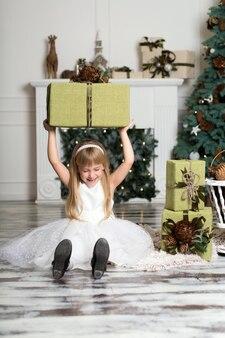 彼女の頭の上にギフトの大きな箱を持って幸せな女の子