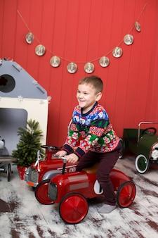 かわいい幼児はおもちゃの赤い車で遊んでいます