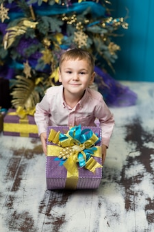幸せな小さな笑みを浮かべて少年はクリスマスギフトボックスを保持します