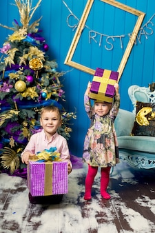 かわいい女の子と男の子は笑みを浮かべて、クリスマスツリーの下のプレゼントを保持しています。