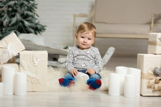 Портрет милый малыш играет на полу возле елки