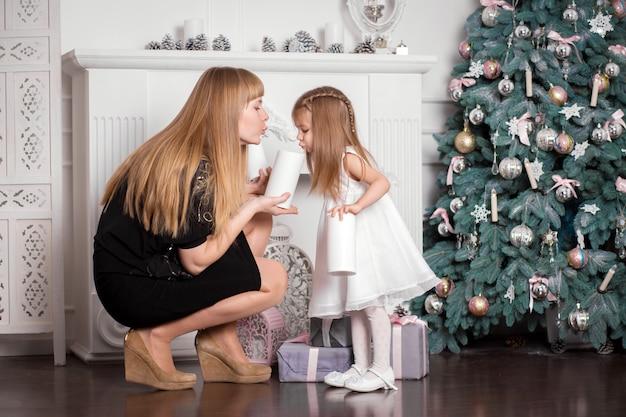 ママは女の子に装飾的なろうそくを示しています