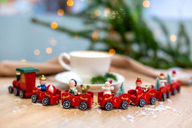 装飾的なクリスマストレイン、赤い装飾品、ホタル、スプルースの枝と木製のテーブルの上の白いセラミックカップでおいしい新鮮なお祝いの朝カプチーノコーヒー
