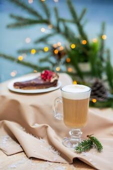 木製のテーブル、ホタル、トウヒの枝にガラスのカップとカップケーキのデザートでおいしい新鮮なお祝いの朝カプチーノコーヒー
