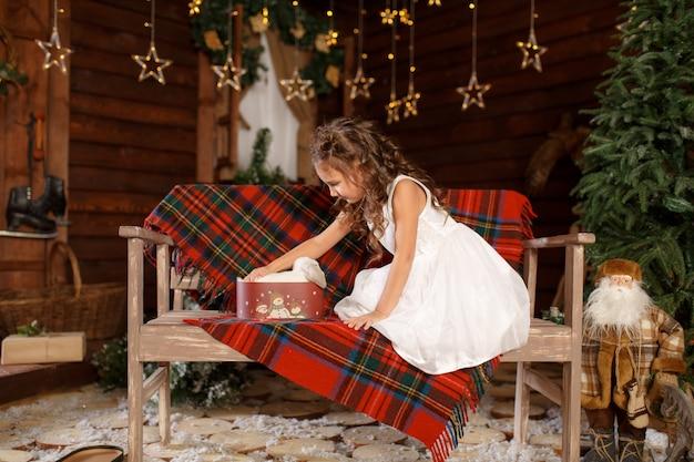 白いウサギのベンチとオープンボックスに座っている白いドレスの少女