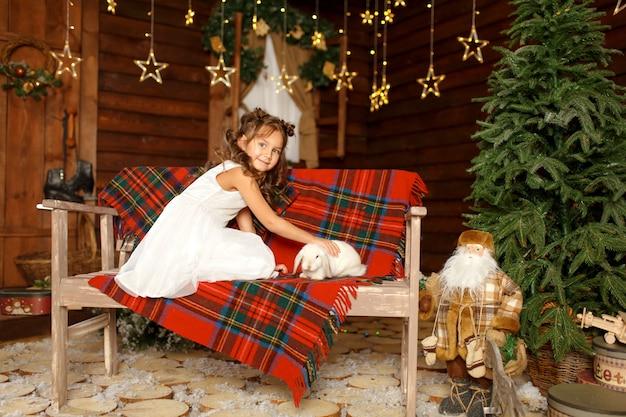白いウサギとベンチに座っている白いドレスの少女