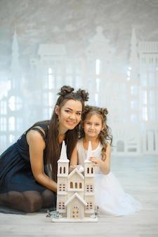 Маленькая девочка с мамой играет в сказочном белом городке