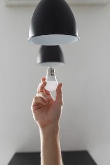 Замена лампочки на светодиодную в торшере черного цвета. на светло-сером фоне