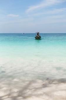 Вид с чистого песчаного пляжа на лодку в голубой лагуне.