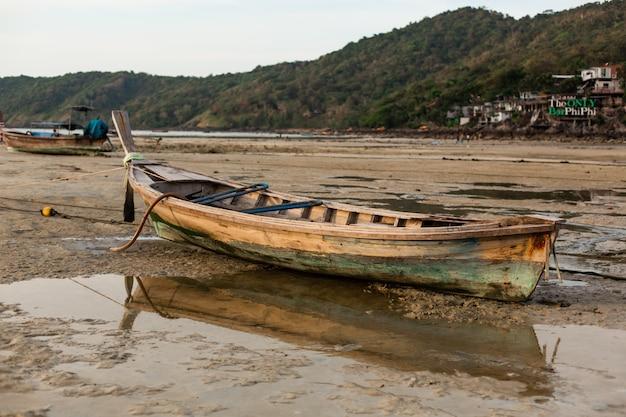 Деревянная рыбацкая лодка сидела на песчаном дне океана во время отлива.