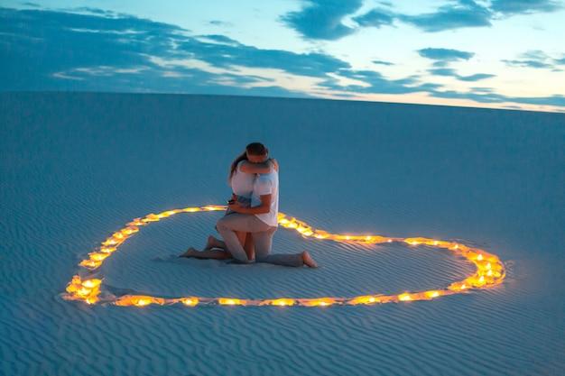 愛のカップルは、砂の砂漠で抱擁します。夕方、ロマンチックな雰囲気、砂の中にハートの形のろうそくを燃やす