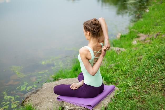 Молодая красивая кавказская девушка брюнет делая йогу на зеленой лужайке на фоне реки