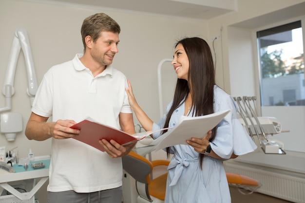 医師と彼の助手は紙でフォルダーを探しています。歯科医院の背景。