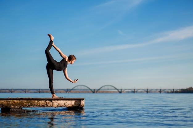都市の背景を持つ静かな木製の桟橋でヨガの練習の若い女性。都市ラッシュのスポーツとレクリエーション