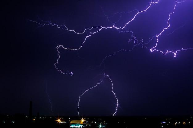 Буря молний над городом в фиолетовый свет.