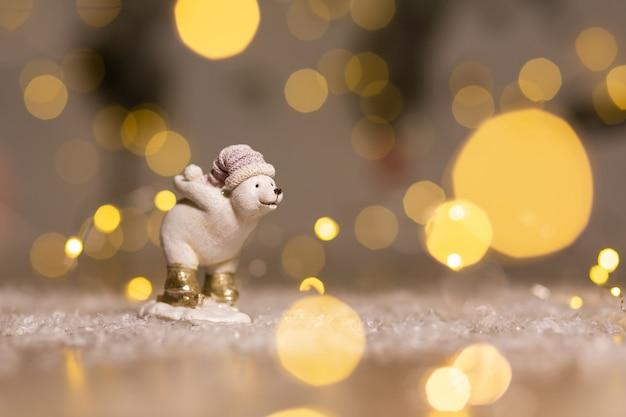 白いクマの子の像は、お祝いの装飾、暖かいボケライトの背後に雪だるまを持っています。