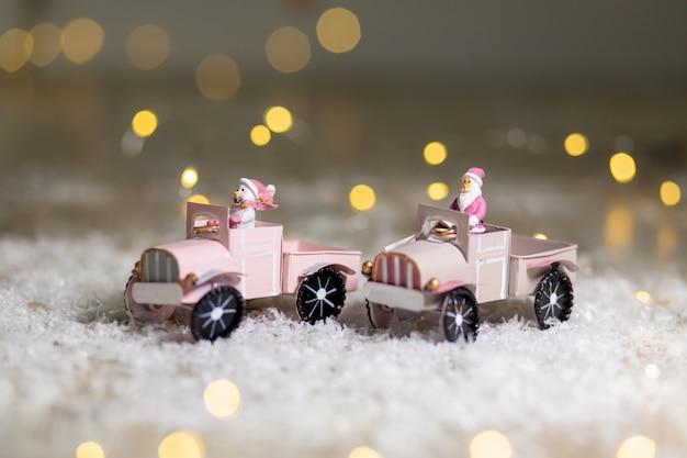 Статуэтка санта катается на игрушечной машинке с прицепом для подарков. праздничный декор, теплые огни боке.