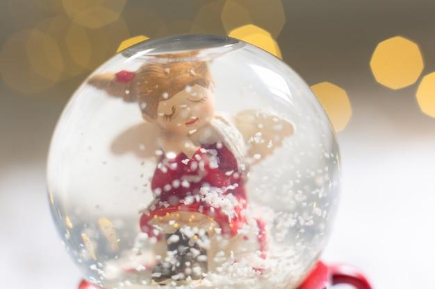Стеклянный шарик со снежинками, внутри которого сидит рождественский ангел праздничный декор, теплые огни боке