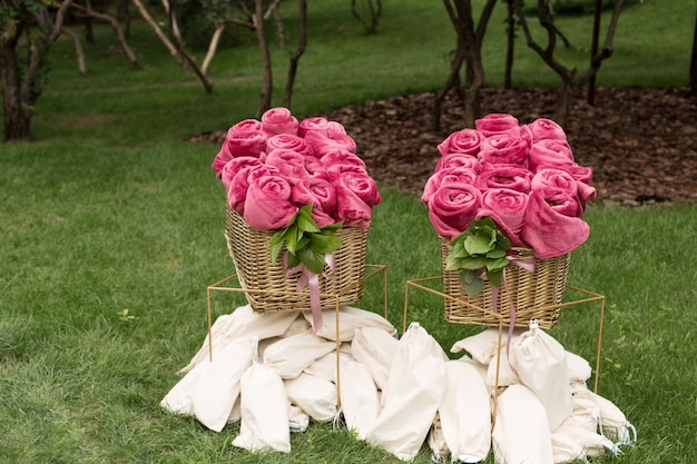 屋外の結婚式パーティーのゲストのために、大きなバスケットにバラの形で巻かれた暖かいピンクの毛布