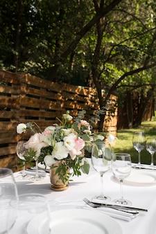 Сервировка свадебного стола украшена живыми цветами в медной вазе