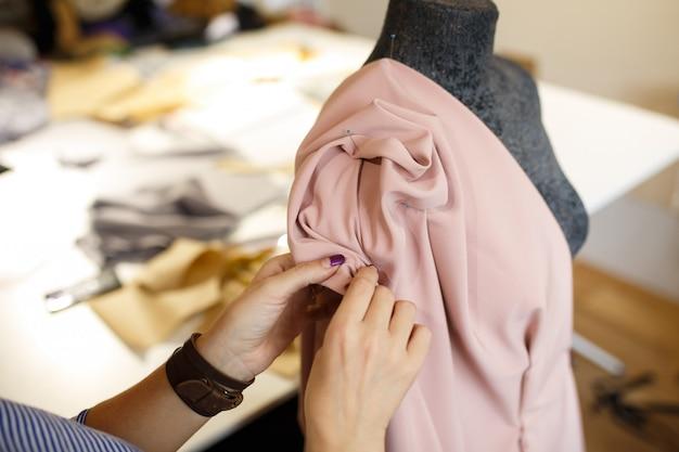 女性のドレスメーカーは、針で生地をマネキンに取り付けます。ドレスデザインの作成