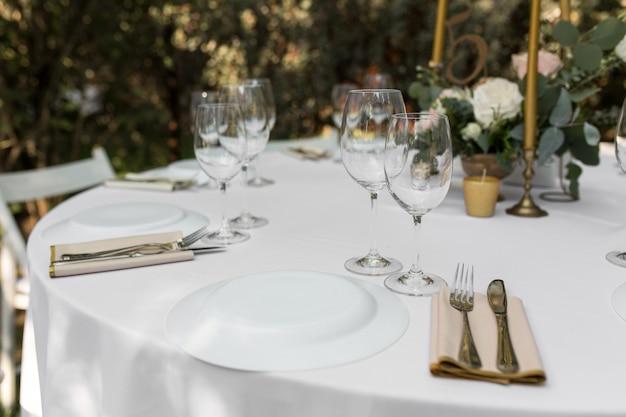 緑の自然の景色を望む屋外のゲスト用の宴会テーブル