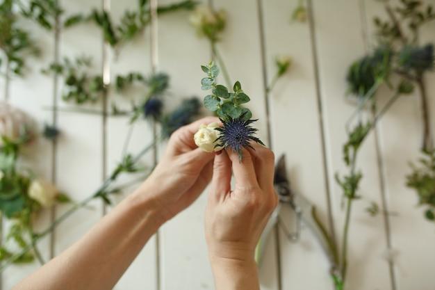 Женщина флористом руки собирает цветы для бутоньерки жениха. флорист рабочий процесс