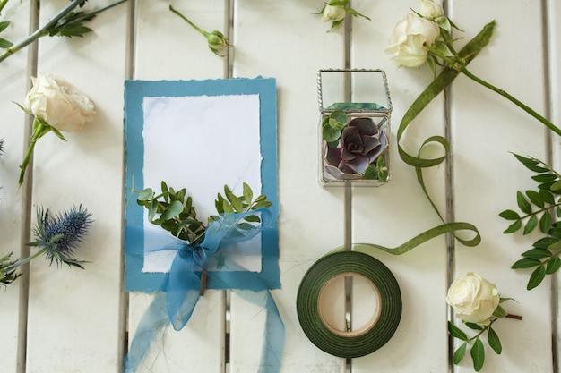 Свежие белые розы и свадебные приглашения на белом деревянном столе. оформление живых цветов