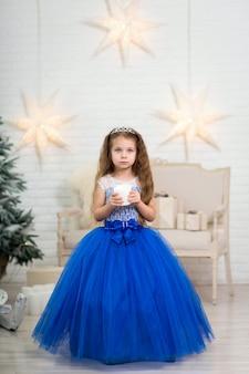 Милая маленькая девочка в пышном голубом платье держит искусственную свечу в руках для украшения дома на рождественские праздники. благоприятные для детей декорации