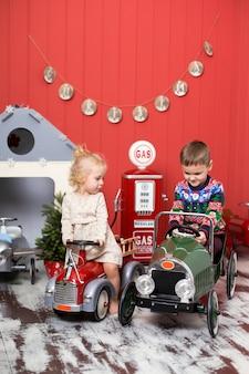 かわいい男の子と女の子が遊ぶし、おもちゃの車に乗る。幸せな子供時代