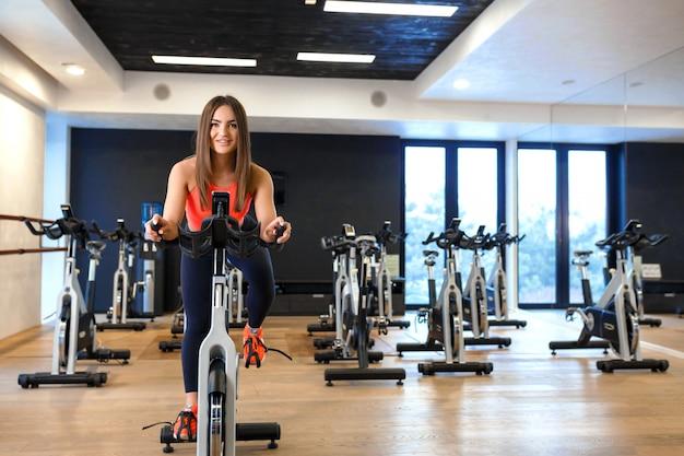 Портрет молодой стройной женщины в спортивной тренировки на велотренажере в тренажерном зале. концепция спортивного и оздоровительного образа жизни