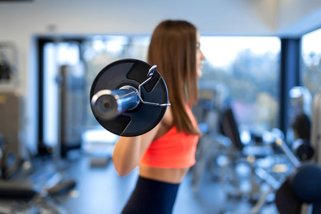 スポーツウェアのスリムなハンサムな若い女性は、ジムで肩にバーベルをスクワットします。