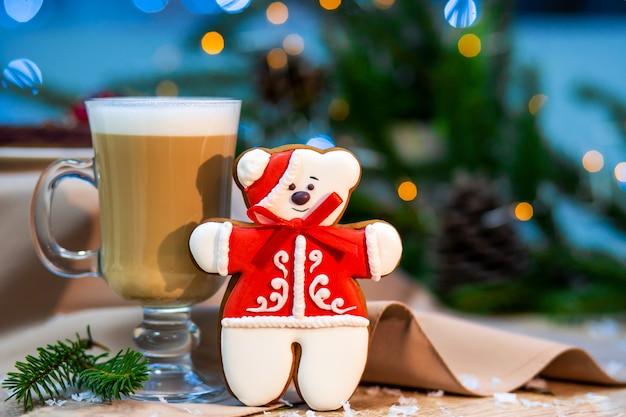 Чашка очень вкусного капучино стеклянная с печеньем пряника плюшевого медвежонка рождества.