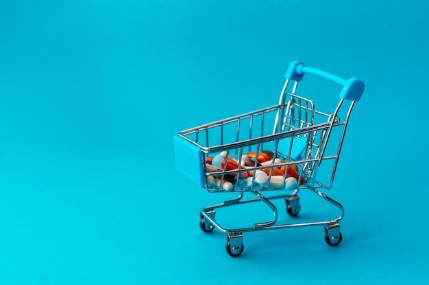 Корзина из супермаркета, наполненная цветными таблетками. медицинская концепция. покупки в аптеке.