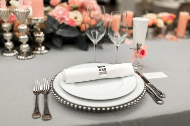 Часть стильной сервировки стола с тарелкой и столовыми приборами.