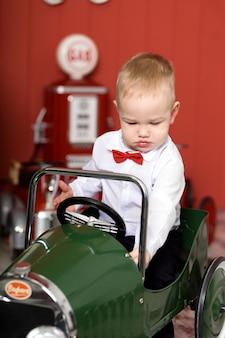 かわいい幼児はおもちゃの車で遊んでいます。おもちゃのタイプライターの飛行機に乗る。幸せな子供時代