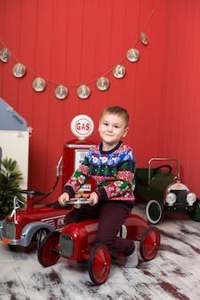 幼児はおもちゃの赤い車で遊んでいます。