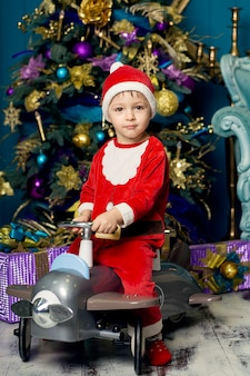 サンタクロースの衣装を着た小さな男の子が飛行機の形のおもちゃの車に乗る。