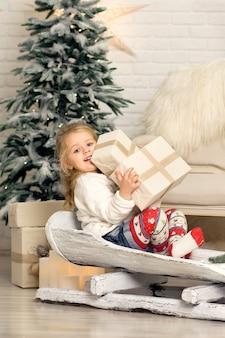 Девушка на санках с рождественской подарочной коробке.