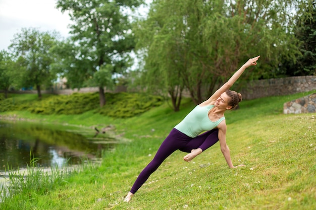 細いブルネットの少女はスポーツをし、夏の公園で美しく洗練されたヨガのポーズを実行します。