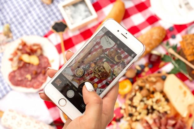 Женщина берет фотографию на свой мобильный телефон во время пикника на открытом воздухе.
