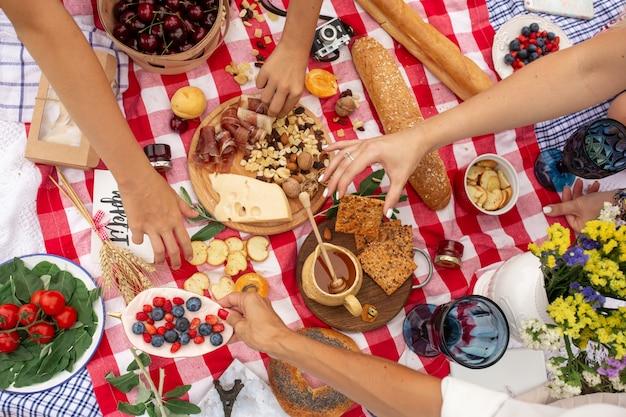 トップビューの人々は、市松模様のピクニックブランケットから食べ物を取ります。