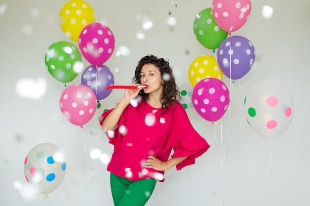 色の風船で美しいかわいい陽気な女の子が笑い、紙吹雪を投げる