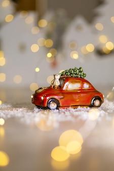 Статуэтка красного автомобиля, на котором сидит плюшевый мишка.